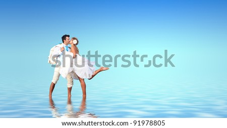 Bride and groom in the sea with water reflection
