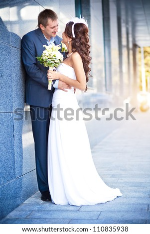 bride and groom is kissing near the  modern building granite wall