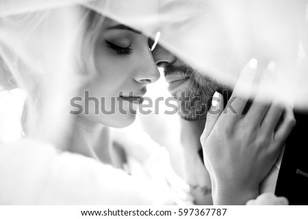 Bride and groom kisses tenderly in the shadow of a flying veil .beautiful pictures. guys enjoy. Sexy kissing stylish couple of lovers close up portrait  . black and white   #597367787