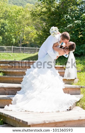 Bride and groom kissing and hugging on green