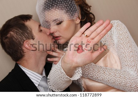 Bride and groom kissing and the hand drawn heart and says \