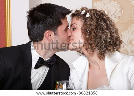 stock photo Bride and groom kissing at the wedding table