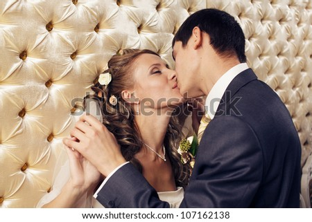 Bride and groom kissing in restaurant. - stock photo
