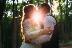 bride and groom kissing in the forest and sun rays between them. profile of newlyweds in the forest.
