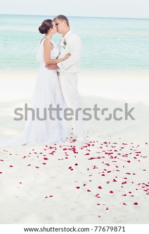 Bride and groom kissing on the tropical beach