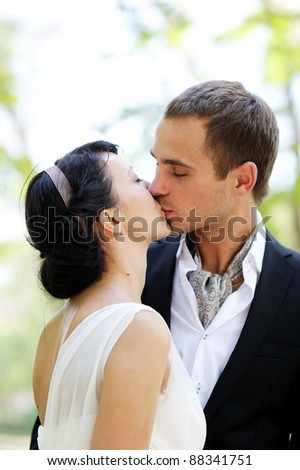 Bride and groom kissing outdoors in the park