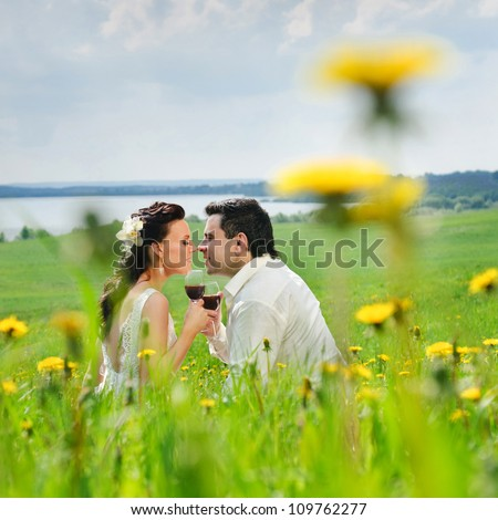 Bride and Groom kissing with a glasses in the field of dandelion