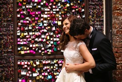 Bride and groom near a gate full with padlocks