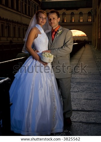 Bride and groom near the river at sunset time