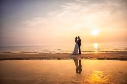 Bride and groom, newlyweds, honeymoon on the beach sunset sun