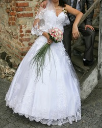 Bride and groom next to wooden stairs and brick wall. Cropped view.
