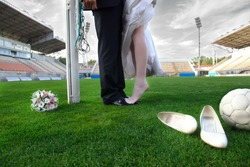 Bride and groom on football stadium with soccer ball