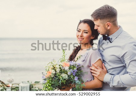 Bride and groom on the beach near the table decorations. Bride holding a beautiful bouquet. #529002955