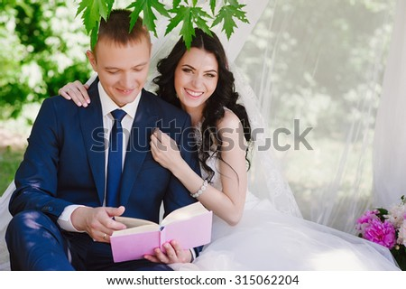 Bride and groom outdoors smiling cuddling and reading books, decor, peonies, flowers, lifestyle, marriage, family, love