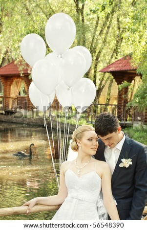 Bride and groom outdoors with white balloons against blurred pond with black swan