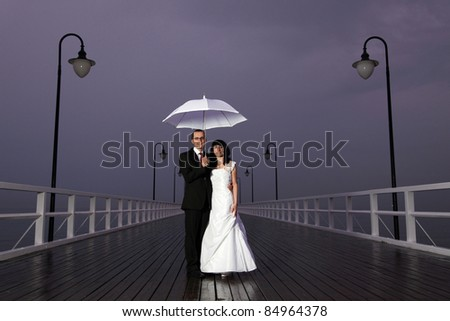 bride and groom, pier cloudy dusk sky.