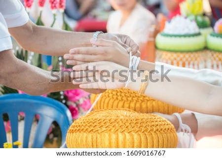 Bride and groom praying hand with holy thread blessing for happiness in their new family life.Thailand traditional wedding and engagement decoration accessories