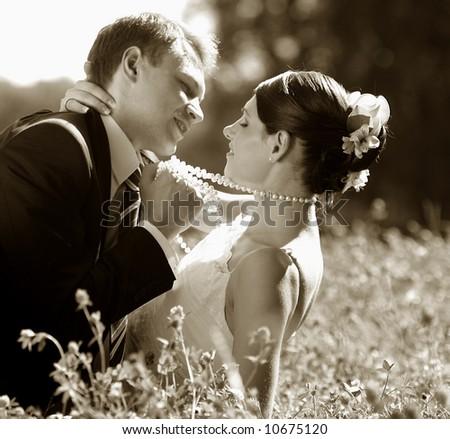 Bride and groom romancing in field