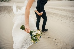 bride and groom run on the beach in wedding dresses. the bride is holding a bouquet of flowers in her hands; there is a gold wedding ring on her hand. Windy weather
