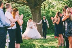 bride and groom running between guests lines
