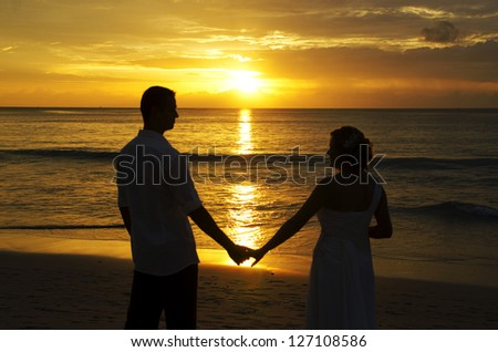 bride and groom silhouette on the beach with sunset background