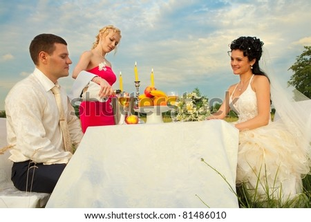 stock photo Bride and groom sitting at wedding table on the field