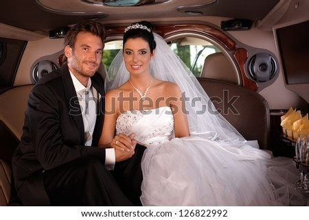 Bride and groom sitting happily in limo on wedding-day.