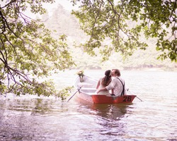 bride and groom sitting in an orange row boat floating out of the tree covering and in to the lake