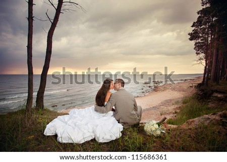 Bride and groom sitting on the beach and kissing.