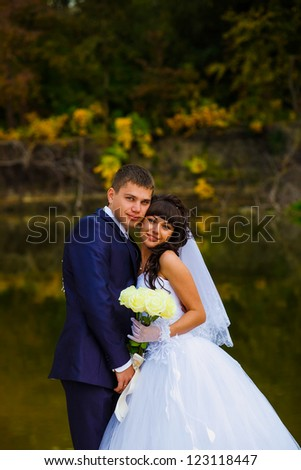 bride and groom standing at the water behind the yellow leaves fall, newlyweds at the wedding