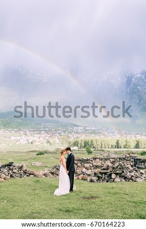 Bride and groom standing in the mountains with rainbow background
