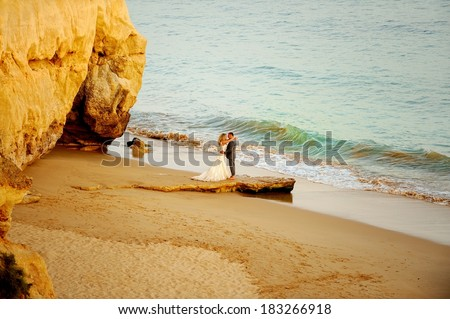 Bride and groom standing on the beach by the beautiful caves and looking at each other.