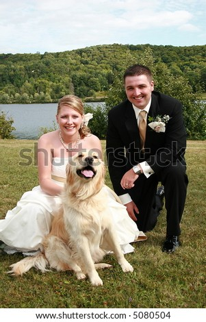 Bride and groom taking a wedding portrait with their pet golden retriever