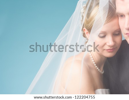 Bride and groom under a veil, romantic moment, blue background and text space