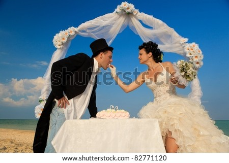 Bride and Groom Under Archway on Beach with wedding cake. Bride giving a bit of cake to groom