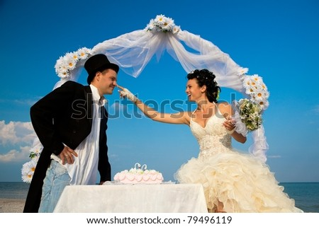 Bride and Groom Under Archway on Beach with wedding cake. Bride putting bit of cake on groom's nose