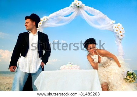 Bride and Groom Under Archway on Beach with wedding cake. Bride trying bit of cake and looking around that nobody see