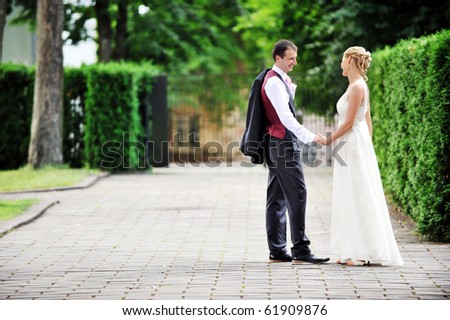 bride and groom walking along the street - stock photo