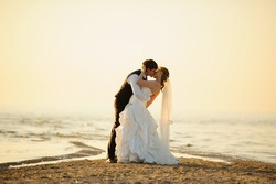 bride and groom walking on the sand at sunset