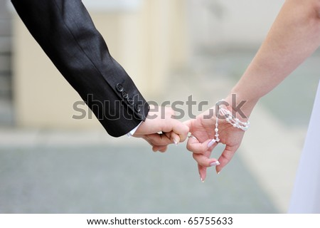 Bride and groom walking together holding their hands