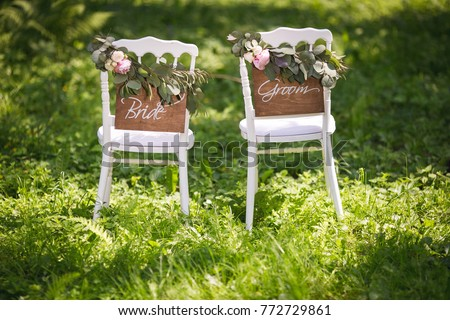 Bride and groom. Wedding bride and groom Signs on chairs standing in the woods.