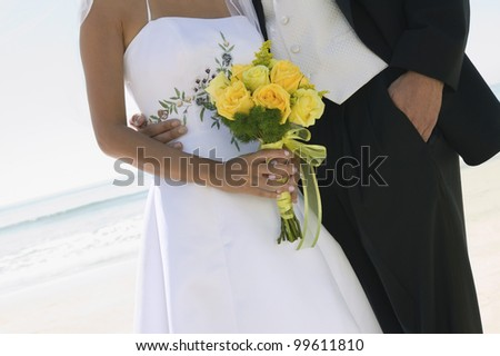 Bride and Groom With Bouquet on Beach