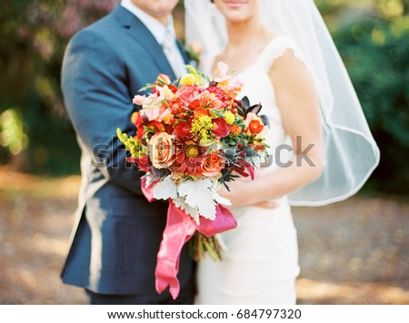 Bride and Groom with Colorful Wedding Bouquet Made of Pink, Orange, Red and Purple Flowers