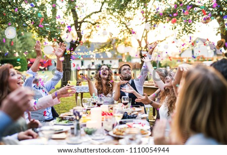 Bride and groom with guests at wedding reception outside in the backyard. #1110054944