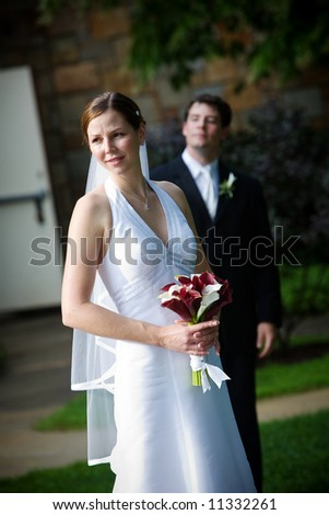 Bride and groom with the man behind his wife during a wedding