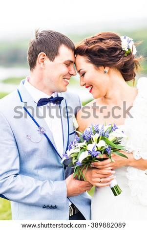 bride and groom with wedding bouquet #389882089