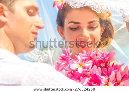 bride and groom, young loving couple, on their wedding day, outdoor beach wedding on tropical beach and sea background #276524258