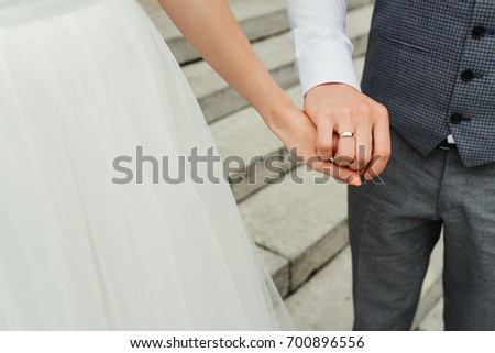 Bride and holding hands at wedding day. Close-up. Wedding ring #700896556