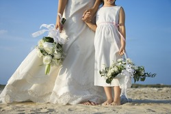 Bride and young flower girl stand on the sandy beach holding hands. Horizontal shot.