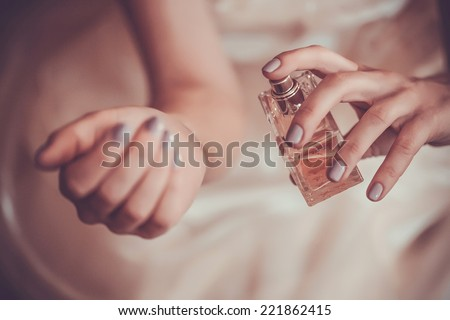 bride applying perfume on her wrist - Shutterstock ID 221862415